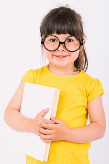 Улыбающаяся маленькая девочка в желтой футболке и круглых черных очках с книгой в руках на белом фоне