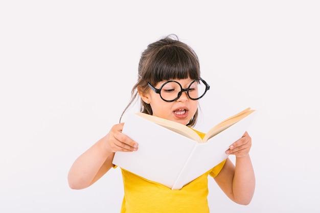 Улыбающаяся маленькая девочка в желтой футболке и круглых черных очках держит в руках открытую книгу и читает вслух на белом фоне