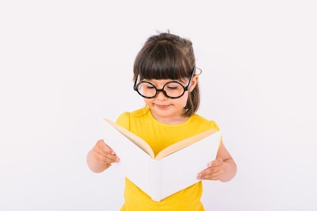 Улыбающаяся маленькая девочка в желтой футболке и круглых черных очках держит в руках открытую книгу и читает на белом фоне