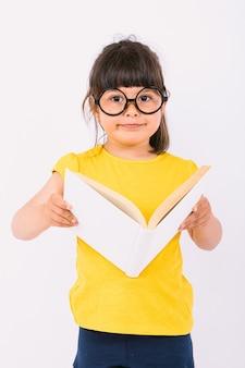 Улыбающаяся маленькая девочка в желтой футболке и круглых черных очках держит в руках открытую книгу на белом фоне