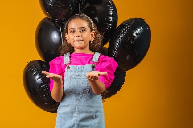 검은 금요일에 검은 풍선과 함께 웃는 어린 소녀. 저렴한 가격의 축제