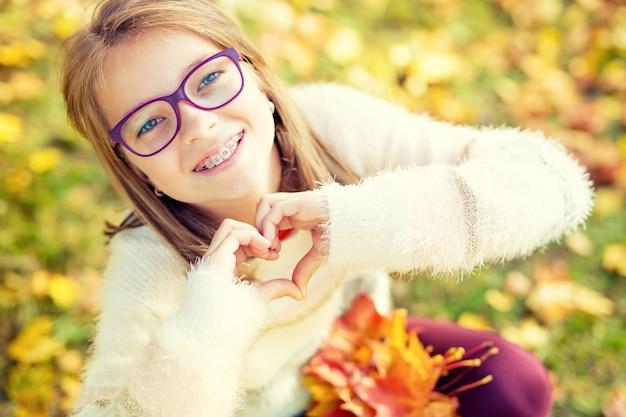 Улыбающаяся маленькая девочка с подтяжками и очками, показывая сердце руками
