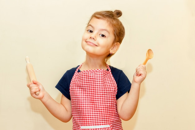Smiling little girl with chef apron holding wooden rolling pin and a spoon on beige background