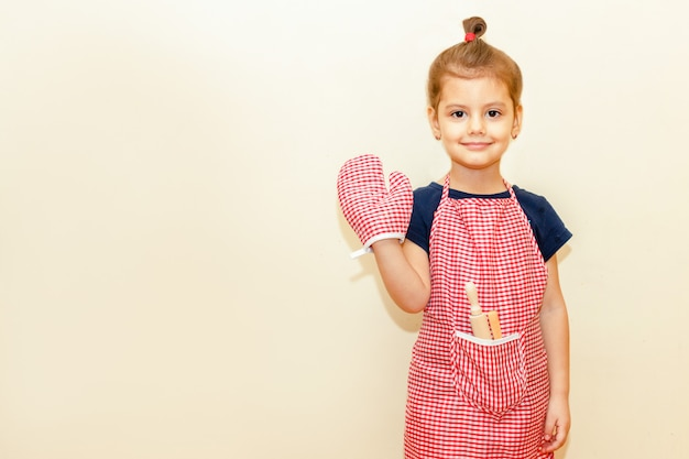Smiling little girl with chef apron and potholder, wooden rolling pin and a spoon on beige background
