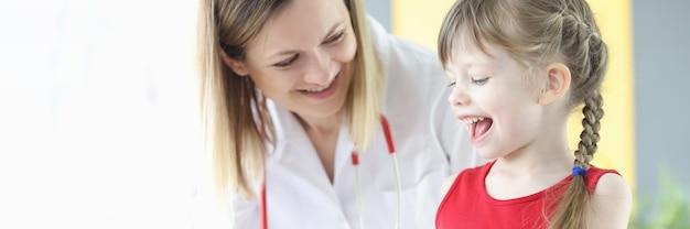 医師の小児科医と笑顔の少女は、透明なカプセルを見ています。子供のビタミン複合体の概念の受容