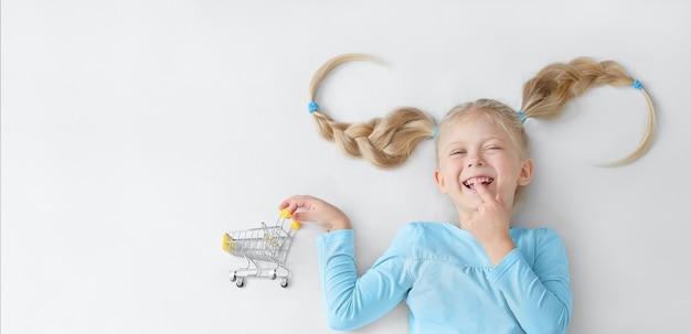 재미있는 머리 스타일과 그녀의 손에 쇼핑 카트 웃는 어린 소녀
