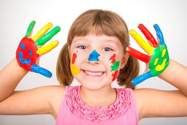 화려한 물감으로 칠한 손으로 웃는 소녀 프리미엄 사진