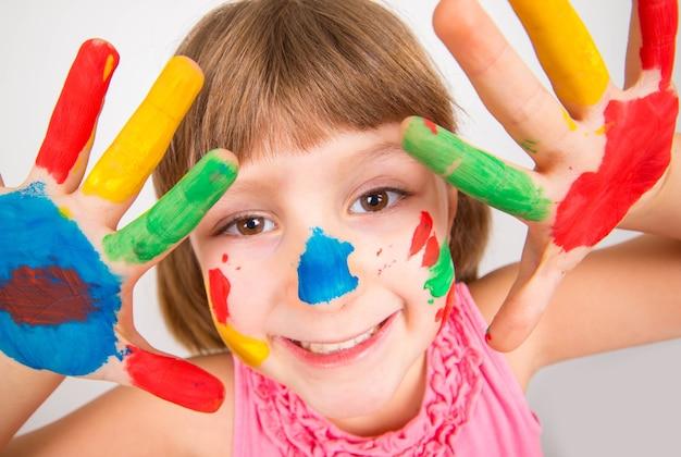 カラフルな絵の具で描かれた手で笑顔の少女