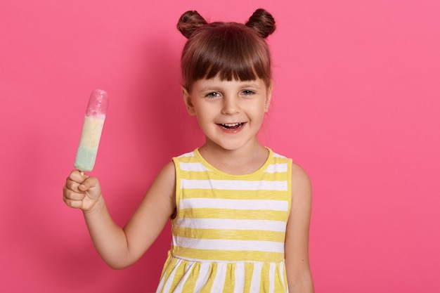 Smiling little girl with ice cream posing isolated over rose wall with joyful expression, holding water ice in hands, funny female kid with knots, wearing summer dress.