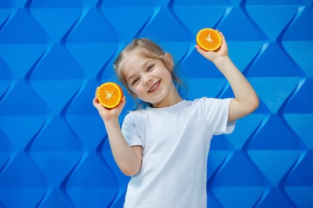 파란 배경에 흰색 티셔츠를 입은 땋은 머리를 한 웃는 어린 소녀와 손에 자른 오렌지가 있습니다. 아이들의 감정, 재미