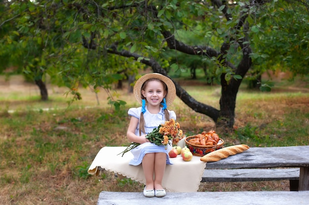 Smiling little girl with two pigtails on her head and in straw hat holding a bouquet of flowers on picnic in garden. summer vacation.