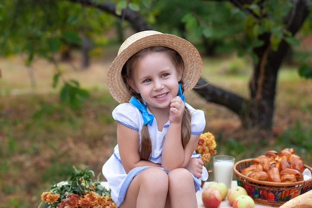 Smiling little girl with two pigtails on her head and in straw hat on  picnic in garden. summer vacation.