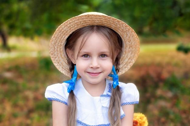 彼女の頭と庭の麦わら帽子の2つのおさげ髪の少女の笑顔。子供と自然。夏休み
