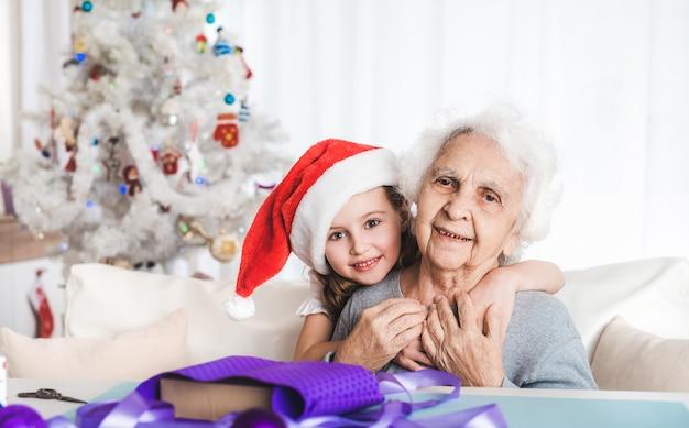 クリスマスにサンタの帽子で笑顔の小さな孫娘がおばあちゃんと抱き締めて座っています
