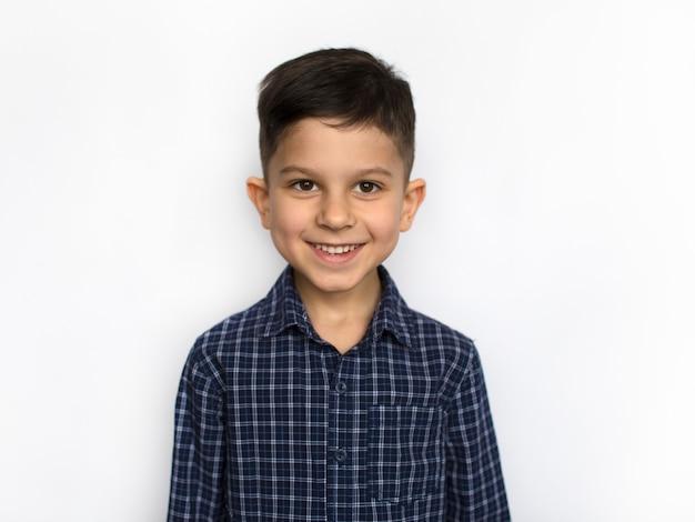 Улыбающийся маленький счастливый мальчик, глядя на портрет камеры, изолированные на белом фоне