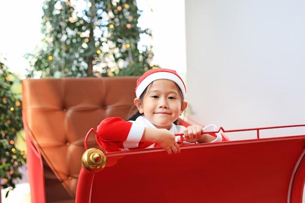 Smiling little kid girl in santa costume dress sitting on red sledge.  merry christmas.