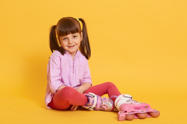 Smiling little kid with two funny ponytail looking directly at camera wit happy look