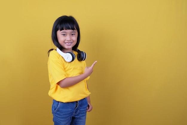 오른쪽을 가리키는 작은 아이 미소, 노란색에 헤드폰 사용