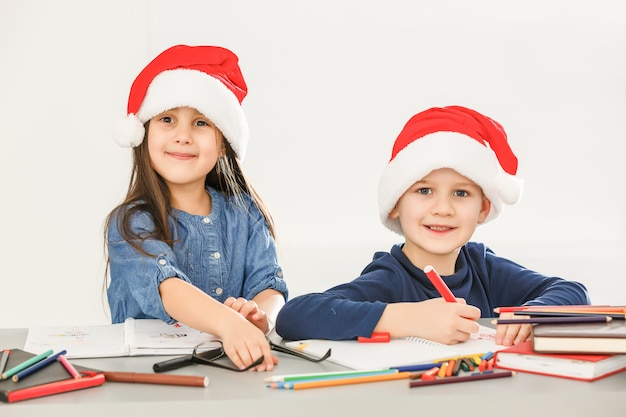 Smiling little kids at the table drawing with crayons with santa hat
