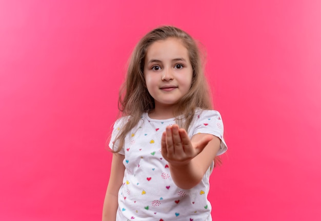 격리 된 분홍색 배경에 손을 밖으로 개최 흰색 티셔츠를 입고 웃는 학교 소녀