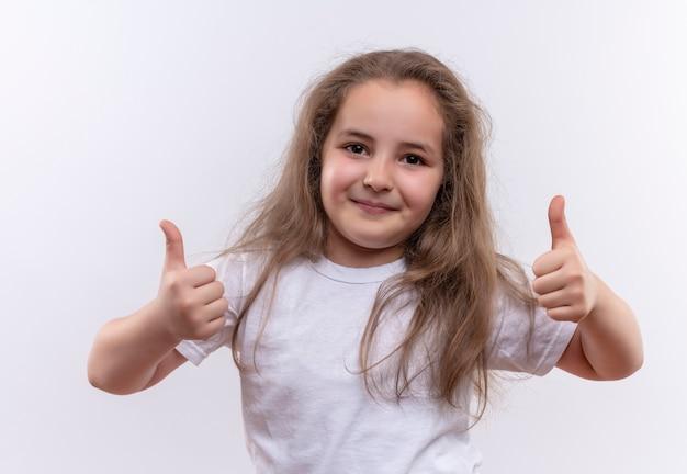 Maglietta bianca da portare della bambina sorridente della scuola i suoi pollici in su su fondo bianco isolato