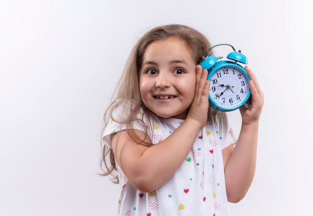 Smiling little school girl wearing white t-shirt holding alarm clock around ear on isolated white background