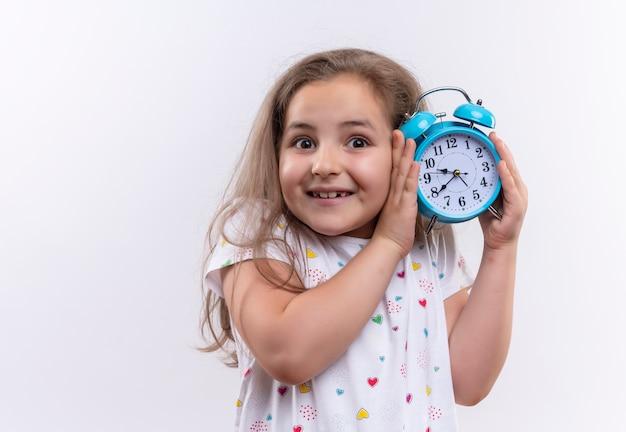 Улыбающаяся маленькая школьница в белой футболке держит будильник вокруг уха на изолированном белом фоне