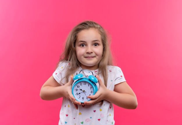 Smiling little school girl wearing white t-shirt holding alarm clock on isolated pink background