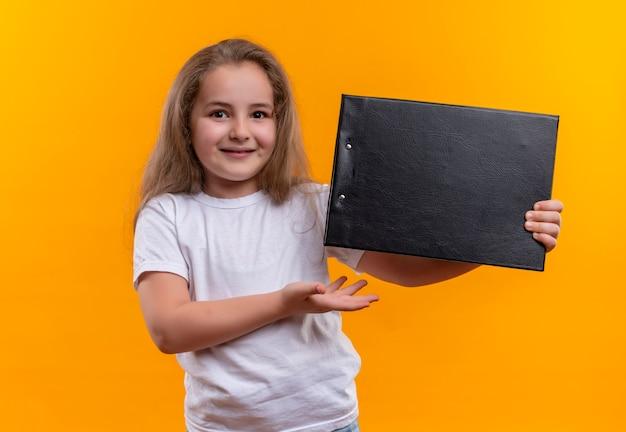 Piccola ragazza sorridente della scuola che porta la lavagna per appunti bianca della tenuta della maglietta su fondo arancio isolato