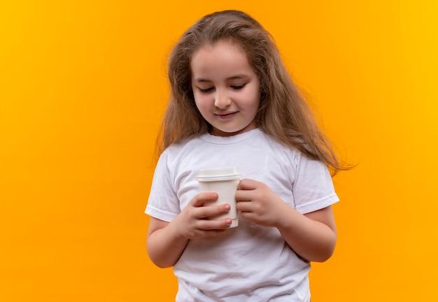 Piccola ragazza sorridente della scuola che indossa la maglietta bianca che tiene tazza di caffè su fondo arancio isolato