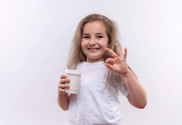 Piccola ragazza sorridente della scuola che porta la tazza di caffè della tenuta della maglietta bianca che mostra il gesto okey su fondo bianco isolato