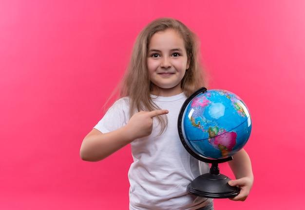 Piccola ragazza sorridente della scuola che porta il globo bianco della tenuta della maglietta su fondo rosa isolato