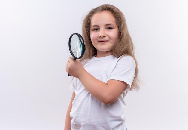 Piccola ragazza sorridente della scuola che indossa la lente d'ingrandimento della tenuta della maglietta bianca su fondo bianco isolato
