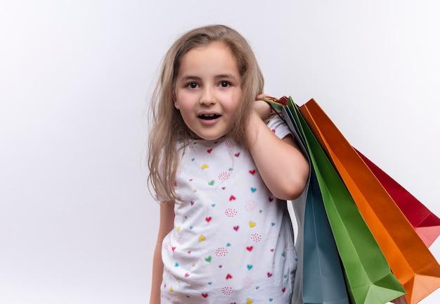 Bambina sorridente della scuola che indossa la maglietta bianca che tiene i sacchetti di carta sulla sua spalla su fondo bianco isolato