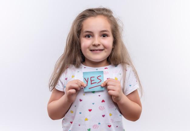 孤立した白い背景に紙のマークを保持している白いtシャツを着て笑顔の小さな女子高生