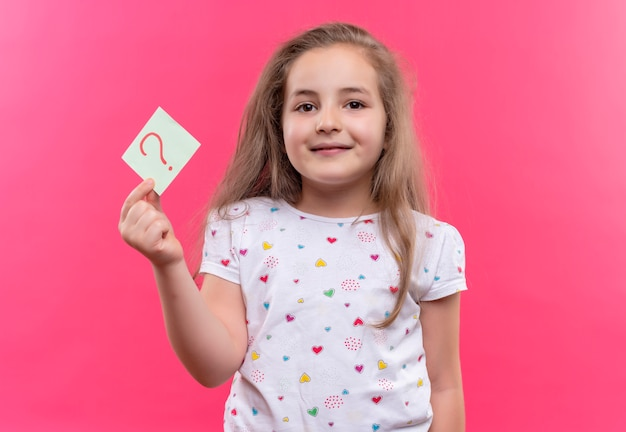 Smiling little school girl wearing white t-shirt holding paper question mark on isolated pink background