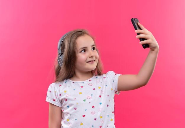 孤立したピンクの背景でselfieを取っているヘッドフォンで白いtシャツを着て笑顔の小さな女子高生
