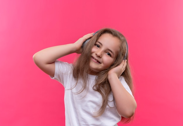 La piccola ragazza sorridente della scuola che porta la maglietta bianca ascolta la musica dalle cuffie su fondo rosa isolato
