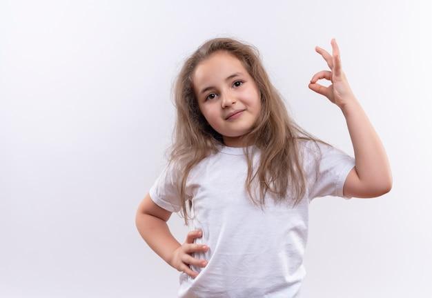 Улыбающаяся маленькая школьница в белой футболке положила руку на бедро, показывая жест на изолированном белом фоне