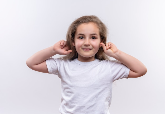 Smiling little school girl wearing white t-shirt put her hands around ears on isolated white background