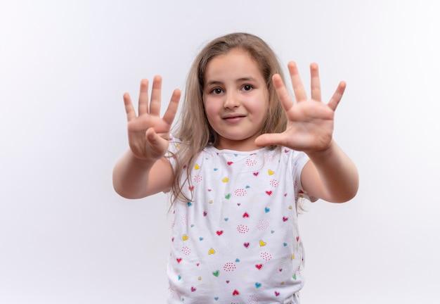 Maglietta bianca da portare della bambina sorridente della scuola che mostra i numeri differenti su fondo bianco isolato