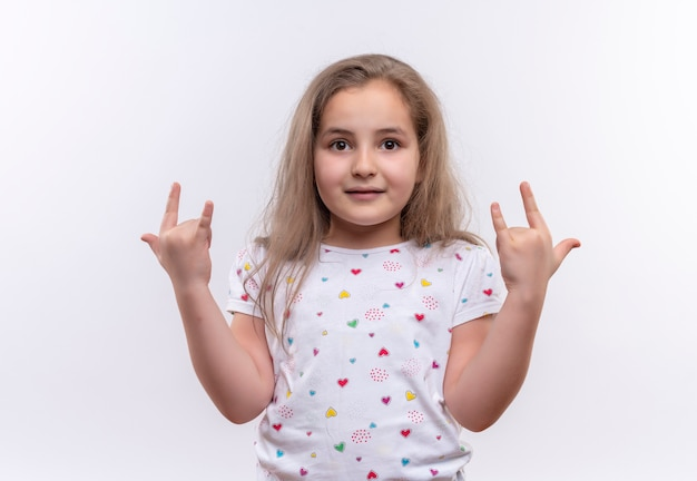 Smiling little school girl wearing white t-shirt showing goat gesture on isolated white background