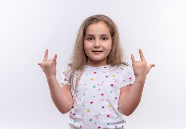 Улыбающаяся маленькая школьница в белой футболке показывает жест козла на изолированном белом фоне