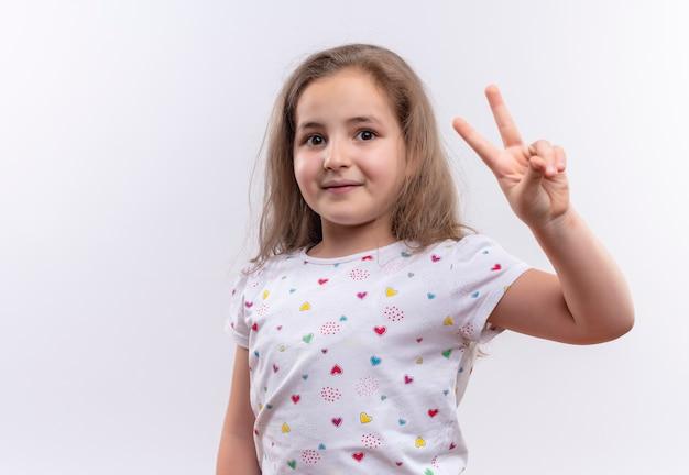 격리 된 흰색 배경에 평화 제스처를 보여주는 흰색 티셔츠를 입고 웃는 어린 학교 소녀