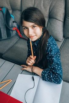 Улыбающаяся маленькая школьница делает домашнее задание перед ноутбуком. дистанционное обучение.