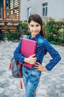Улыбающаяся маленькая школьница с ноутбуком в руке, снова в школу и концепция успешной женской карьеры