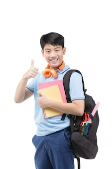 Smiling little student boy in blue polo t-shirt in with books and bag.