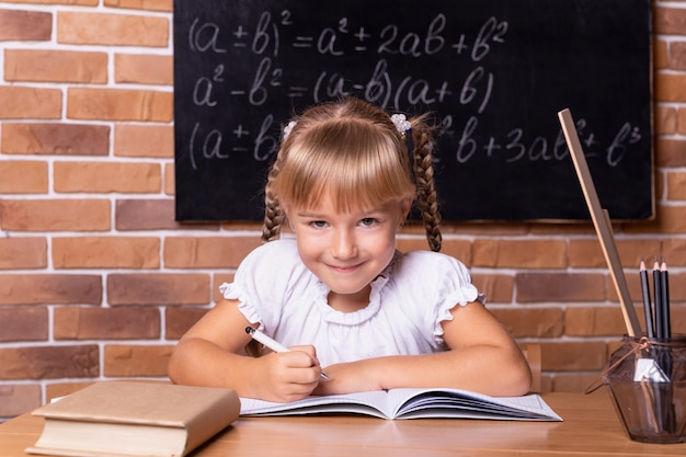 Улыбающаяся маленькая студентка сидит за партой и изучает математику