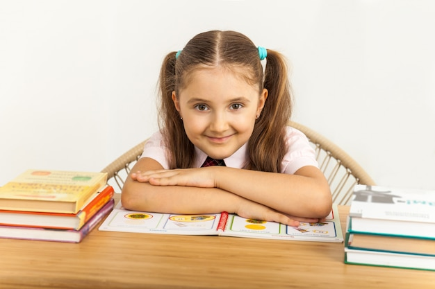 Smiling little student girl with many books at school