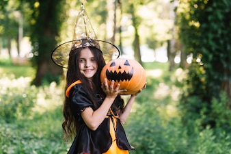 Smiling little witch holding pumpkin